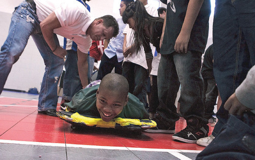 Leah Hogsten     The Salt Lake Tribune   Skeleton athlete Steve Jackson shows Lied Club member Mohamed Haji, 11, the correct way to steer a skeleton sled Thursday as Athletes for Hope's professional athletes and Olympic athletes visited with kids at Boys & Girls Clubs of Greater Salt Lake's Lied Club.