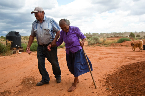 Chris Detrick  |  The Salt Lake Tribune As the wind starts to blow, Albert Cly, 71, walks with Jesse Herderboy outside of her home in Westwater Thursday August 19, 2010. The roughly two-dozen Navajo residents of Westwater, many who are elderly, live without running water, plumbing, sewage disposal or electricity.