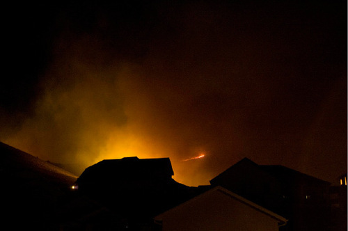 Djamila Grossman  |  The Salt Lake TribuneA wildfire burns behind houses on Emmeline Drive in Herriman, September 19, 2010.  People throughout the area were evacuated and smoke was visible across the valley.