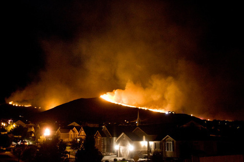 Djamila Grossman  |  The Salt Lake TribuneA wildfire burns in the mountains behind Herriman, September 19, 2010.  People throughout the area were evacuated and smoke was visible across the valley.