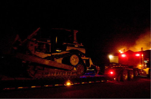Djamila Grossman  |  The Salt Lake TribuneA piece of heavy machinery is moved into an area where a wildfire burns along a ridgeline above Herriman, September 19, 2010.  People throughout the area were evacuated and some houses burned down.