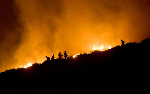 Djamila Grossman  |  The Salt Lake Tribune  Firefighters are seen on a ridgeline where a wildfire burns above Herriman, Sept. 19, 2010.  People throughout the area were evacuated and some houses burned down.
