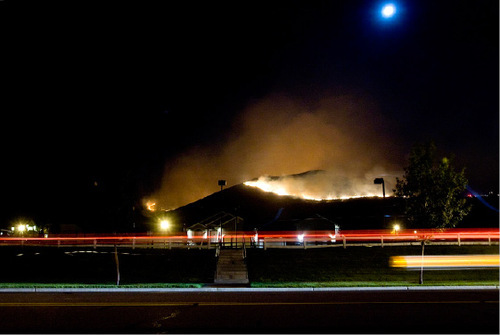 Djamila Grossman  |  The Salt Lake TribuneA car drives by an area where a wildfire burns along a ridgeline above Herriman, on Monday, September 20, 2010.  People throughout the area were evacuated and some houses burned down.