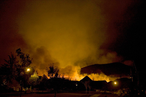 Djamila Grossman  |  The Salt Lake TribuneA wildfire burns along a ridgeline above Herriman, on Monday, Sept. 20, 2010.  People throughout the area were evacuated and some houses burned down.
