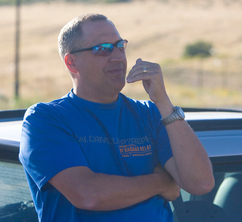 Al Hartmann  |  The Salt Lake TribuneDavid Roth, stake president for the Herriman South Stake, watches as crews put out hot spots Monday behind his home in Herriman.  He was waiting about a half mile down hill for the all-clear signal to return to his home.