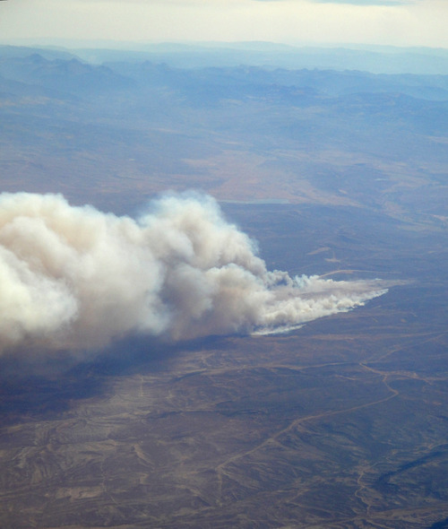 Plumes of smoke billow from the Herriman fire from the window of an Alaskan Airlines flight between Dallas and Seattle, as it crossed over the Salt Lake Valley on Sunday afternoon. Photo courtesy Lorie Dankers.