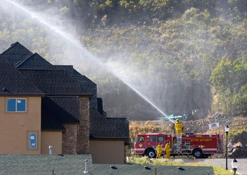 Al Hartmann  |  Salt Lake TribuneUnified Fire fighters hose down some Oak brush Monday morning near the burn line from the Herriman fire.