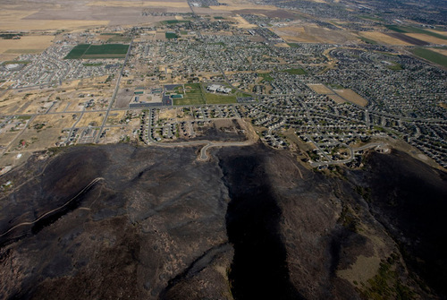 Steve Griffin  |  The Salt Lake Tribune The mountain side south west of Herriman is burned black Monday, September 20, 2010 but flames were stopped short of all but four homes in this subdivision. Crews continued to battle the blaze Monday morning.