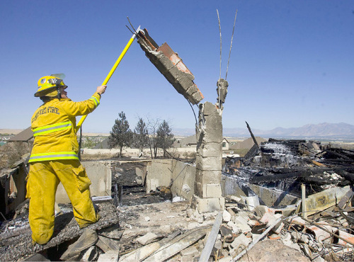 Al Hartmann     The Salt Lake Tribune Engineer Fenton Quinn of the Unified Fire Deptartment pulls down an unstable chimney from the Burnses' destroyed home in Herriman on Monday afternoon.