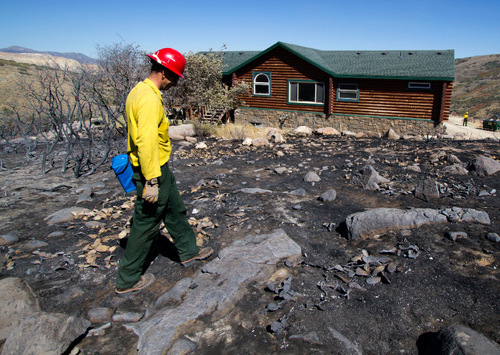 Jason Curry, public information officer with the Sanders Interagency Incident Management Team, walks past a home in Rose Canyon that escaped the flames of the wildfire started by Machine Gun fire in Herriman, Utah, Tuesday, Sept. 21, 2010. The blaze destroyed several homes and forced the evacuation of around 1,600 homes. (AP Photo/Jim Urquhart)