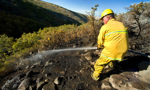 Lehi Fire Department's Capt. Kim Beck hoses down a hillside Monday, Sept. 20, 2010, in Herriman. (Douglas C. Pizac/Special to The Tribune)