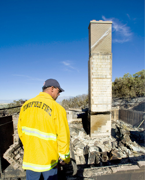 Firefighter Steve Judkins, of Unified Fire, looks over the remains of the Johnson home Monday, Sept. 20, 2010, in Herriman, Utah. (© 2010 Douglas C. Pizac/Special to The Tribune)