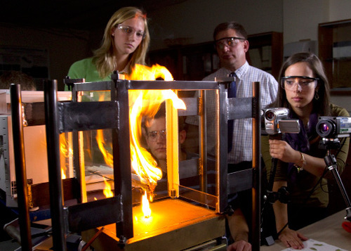 BYU professor of chemical engineering Thomas Fletcher, center, in his lab, simulating a fire front to help predict where wildfires will spread. Also pictured are students Kelsey Gooch and McKaye Dennis. (Mark A. Philbrick)