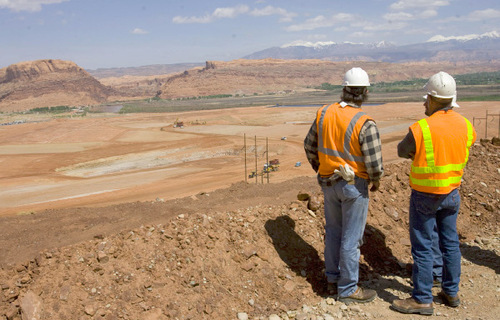 File photo  |  The Salt Lake Tribune  Contractors look down onto the vast uranium-tailings pile next to the Colorado River that will be moved over the next ten years by rail cars to a safe disposal site further north near Crescent Junction. Today the first load of uranim tailings was loaded onto rail cars.
