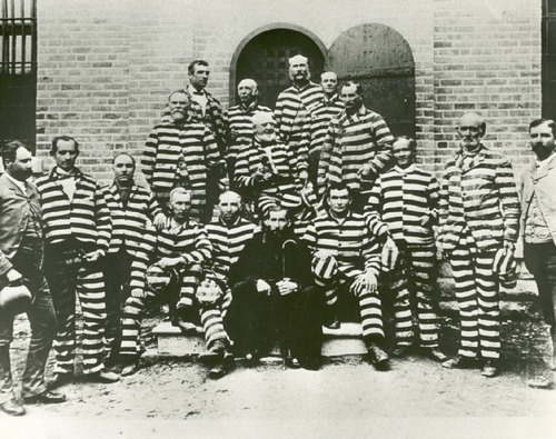 Polygamists including: Joseph Stacey Murdock (2nd row far left with white moustache and goatee), James E. Hamilton (behind Murdock), George Q. Cannnon (2nd row center, right of Murdock), Daniel B. Hill (Third row top right), Amundsen (2nd row right of Cannon),  Hans Jesperson (Bottom row third from far right), and Dow (bottom row far right) Credit: Salt Lake Tribune Library