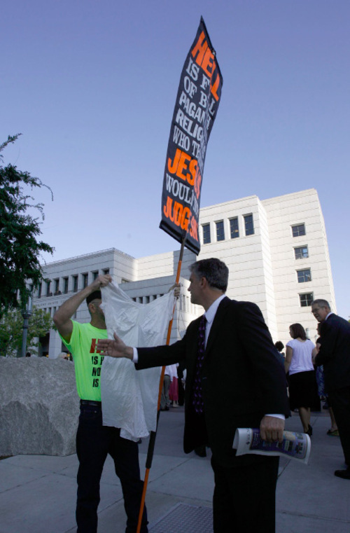 Francisco Kjolseth  |  The Salt Lake TribuneA church member tries to reach out to a protester as members of the Church of Jesus Christ of Latter Day Saints file into the conference center for General Conference on Saturday, Oct. 2, 2010.Salt Lake City Oct. 2, 2010.