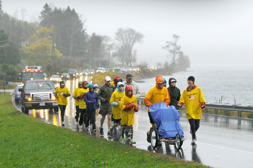 Mike Ehredt, of Hope, Idaho, pushing stroller, runs the final leg of his 4,425-mile coast-to-coast run Friday, Oct. 15, 2010, in Rockland, Maine. Ehredt, an Army veteran, started his run in Astoria, Ore., on May 1. He placed a flag every mile to honor service members lost in Iraq. (AP Photo/Robert F. Bukaty)