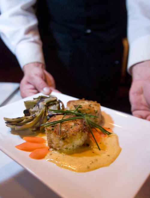 Paul Fraughton  |  The Salt Lake Tribune      A server brings an order of Dungeness  crab cakes  from Spencer's in Salt Lake City's Hilton Hotel on  Friday, Oct. 8, 2010.
