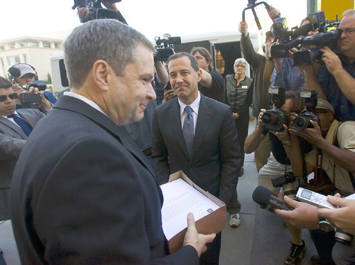 Al Hartmann  |  Salt Lake TribuneScott Trotter, spokesperson for the LDS Church, left, accepts a box of 150,000 signatures on a petition demanding that LDS apostle Boyd K. Packer