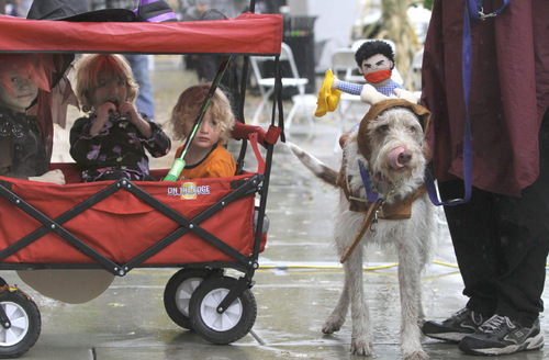 Rick Egan   |  The Salt Lake Tribune  Akane, and Stephanie, Briar Randall and Stitch the dog, try to stay dry at the Witchstock festival on Historic 25th Street in Ogden, Saturday, Oct. 23, 2010.