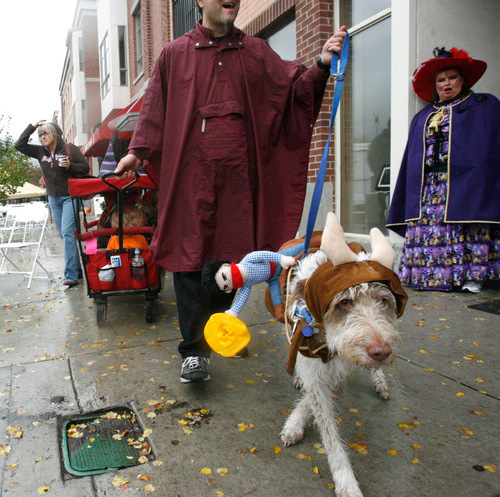 Rick Egan   |  The Salt Lake Tribune Stitch the dog leads the way, Albert Randall pulls the wagon with Akane, Stephanie, Briar inside as they try to stay dry at the Witchstock festival on Historic 25th Street in Ogden, Saturday, Oct. 23, 2010.