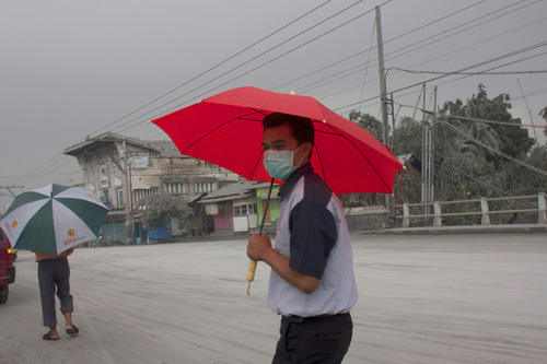 A man walks on a street covered with volcanic ash from the eruption of Mount Merapi in Muntilan, Indonesia, Thursday, Nov. 4, 2010. Indonesia's deadly volcano sent a burst of searing gas high into the air Thursday, hours after its most explosive eruption in a deadly week triggered an exodus from villages and emergency shelters along its rumbling slopes. (AP Photo/Gembong Nusantara)