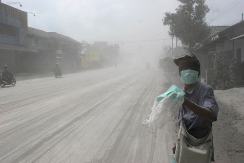 A man sells face masks on an ash-covered street in Muntilan, Indonesia, Thursday, Nov. 4, 2010. Indonesia's deadly volcano sent a burst of searing gas high into the air Thursday, hours after its most explosive eruption in a deadly week triggered an exodus from villages and emergency shelters along its rumbling slopes. (AP Photo/Trisnadi)