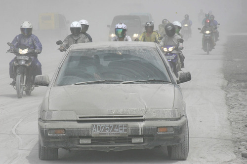 Motorists ride on an ash-covered street in Muntilan, Indonesia, Thursday, Nov. 4, 2010. Indonesia's deadly volcano sent a burst of searing gas high into the air Thursday, hours after its most explosive eruption in a deadly week triggered an exodus from villages and emergency shelters along its rumbling slopes. (AP Photo/Trisnadi)