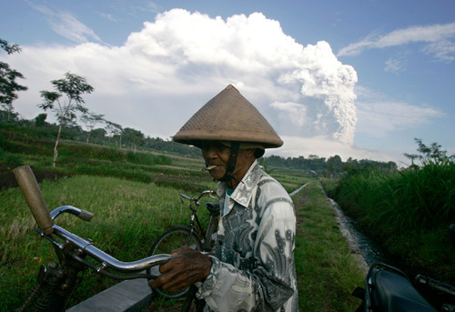 A farmer pushes his bicycle as volcanic material from Mount Merapi eruption is seen in the background in Klaten, Indonesia, Thursday, Nov. 4, 2010. Searing gas and molten lava poured from Indonesia's deadly volcano in an explosion three times as powerful as last week's devastating blast, chasing people from villages and emergency shelters along its slopes. (AP Photo/Irwin Fedriansyah)