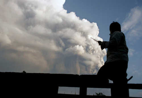 A volunteer watches as Mount Merapi erupts in Sleman, Yogyakarta, Indonesia, Thursday, Nov. 4, 2010. Searing gas and molten lava poured from Indonesia's deadly volcano in an explosion three times as powerful as last week's devastating blast, chasing people from villages and emergency shelters along its slopes. (AP Photo/Slamet Riyadi)