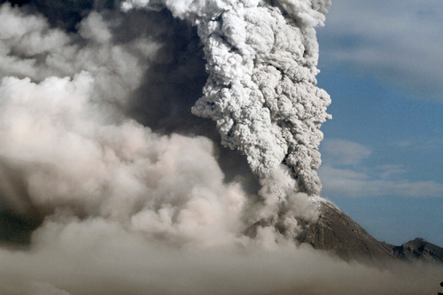 Mount Merapi spews volcanic material as seen from Klaten, Indonesia, Thursday, Nov. 4, 2010. Searing gas and molten lava poured from Indonesia's deadly volcano in an explosion three times as powerful as last week's devastating blast, chasing people from villages and emergency shelters along its slopes. (AP Photo/Irwin Fedriansyah)