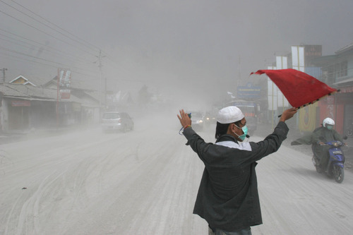 A volunteer directs traffic on an ash-covered street in Muntilan, Indonesia, Thursday, Nov. 4, 2010. Indonesia's deadly volcano sent a burst of searing gas high into the air Thursday, hours after its most explosive eruption in a deadly week triggered an exodus from villages and emergency shelters along its rumbling slopes. (AP Photo/Trisnadi)
