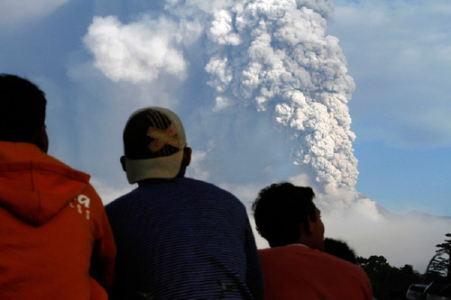 Residents watch as volcanic material from Mount Merapi eruption is seen in the background in Klaten, Indonesia, Thursday, Nov. 4, 2010. Searing gas and molten lava poured from Indonesia's deadly volcano in an explosion three times as powerful as last week's devastating blast, chasing people from villages and emergency shelters along its slopes. (AP Photo/Irwin Fedriansyah)