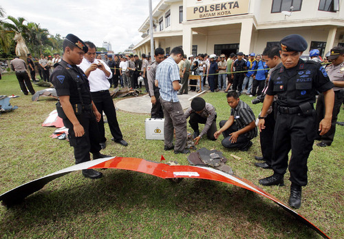 Indonesian police officers inspect parts of a Qantas jetliner that were found in a area, at the local police headquarters in Batam, Indonesia, Thursday, Nov. 4, 2010. The jetliner made an emergency landing Thursday in Singapore with 459 people aboard, after one of its four engines shut down over western Indonesia and following witness reports of a blast that sent debris hurtling to the ground. (AP Photo/Tundra Laksamana)