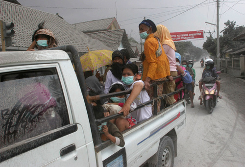 Villagers ride on a truck as they leave their homes on a street covered by volcanic ash from the eruption of Mount Merapi in Muntilan, Indonesia, Thursday, Nov. 4, 2010. Indonesia's deadly volcano sent a burst of searing gas high into the air Thursday, hours after its most explosive eruption in a deadly week triggered an exodus from villages and emergency shelters along its rumbling slopes. (AP Photo/Trisnadi)