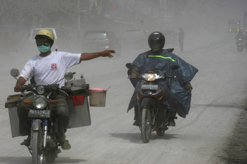 Motorists ride on a street covered with volcanic ash from the eruption of Mount Merapi in Muntilan, Indonesia, Thursday, Nov. 4, 2010. Indonesia's deadly volcano sent a burst of searing gas high into the air Thursday, hours after its most explosive eruption in a deadly week triggered an exodus from villages and emergency shelters along its rumbling slopes. (AP Photo/Trisnadi)