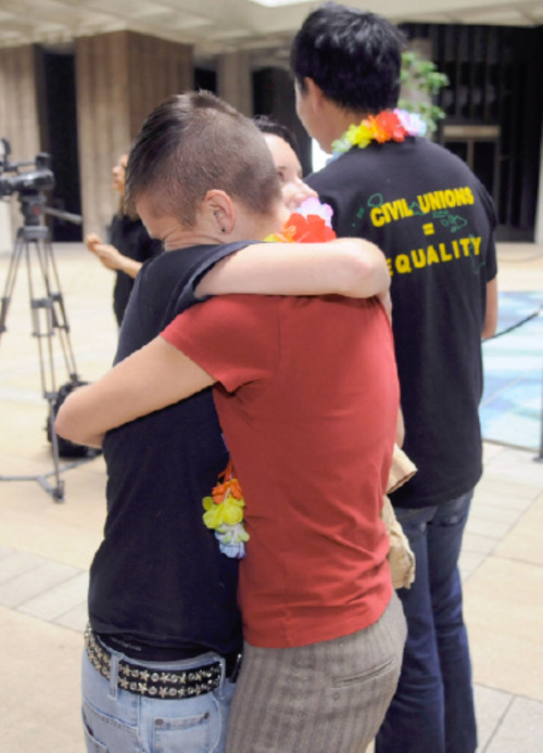 In this April 29, 2010 photo, partners Bridget Murphy, left, and Carlyn Arteaga of Honolulu  hug and celebrate the passing of the civil union bill in Hawaii's  House of Representatives.  Civil unions for Hawaii gay couples could become law early next year as a result of this week's elections. Gay-friendly Democrat Neil Abercrombie will be governor and the Democrat-controlled Legislature survived threats that they'd be voted out of office if they passed the legislation.  (AP Photo/The Honolulu Advertiser, Norman Shapiro)