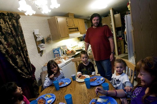 Djamila Grossman  |  The Salt Lake TribuneFrom left: Siblings Destiny Chambers, 10, Ashley Chambers, 8, Dominick Kirkwood, 5, Kason Kirkwood, 4, and Kylie Chambers, 11, eat dinner while Jason Chambers watches, at their Wellington home, Thursday, November 4, 2010. Kylie is on the Children's Health Insurance Program, under whose recent changes in insurers her parents now have to drive more than 60 miles for their daughter to see a doctor.