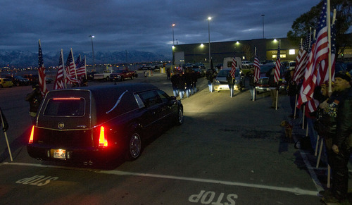 Al Hartmann  |  The Salt Lake Tribune Patriot Riders with American flags salute as the hearse carrying the remains of Cpt. George Willard Grismore as it leaves an air cargo warehouse at Salt Lake City International Airport on Wednesday morning.  Grismore's plane went down in Leyte, Phillipines, on March 12, 1945.  His remains were identified using a DNA match from a family member nearly 65 years later.