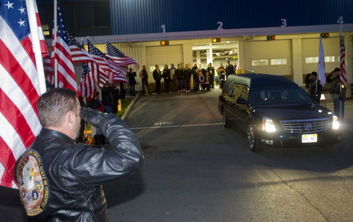 Al Hartmann  |  The Salt Lake Tribune Patriot Riders with American flags salute as the hearse carrying the remains of Cpt. George Willard Grismore leave an air cargo warehouse at the Salt Lake City International Airport on Wednesday morning.  Grismore's plane went down in Leyte, Phillipines, on March 12, 1945.  His remains were identified with a dna match from a family member nearly 65 years later.
