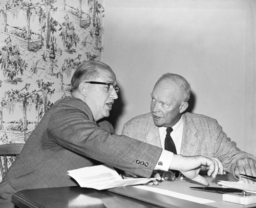 Ezra Taft Benson, left, Secretary of Agriculture, reaches over to get some papers as he meets with President Dwight D. Eisenhower in the president's temporary offices in the Gettysburg Hotel, Aug. 19, 1959. Benson drove to Gettysburg from Washington this morning. (AP Photo/William J. Smith)