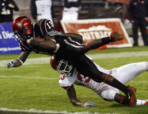 San Diego State's Ronnie Hillman plows over Utah's Justin Taplin-Ross while scoring on a five yard run during the second quarter of a NCAA college football game Saturday, Nov. 20, 2010, in San Diego. (AP Photo/Lenny Ignelzi)