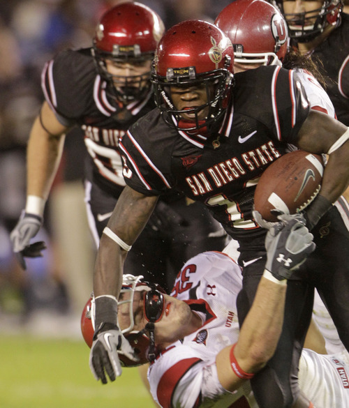 San Diego State's Ronnie Hillman drives through Utah's Greg Bird while gaining five yards during the first half of a NCAA college football game Saturday, Nov. 20, 2010, in San Diego. (AP Photo/Lenny Ignelzi)