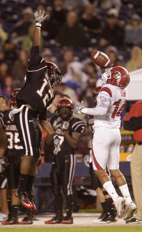 Utah's Reggie Dunn makes a one handed catch as San Diego State's Josh Wade misses the block on a play that resulted in a 42 yard gain during the first quarter  of a NCAA college football game Saturday, Nov. 20, 2010, in San Diego. (AP Photo/Lenny Ignelzi)
