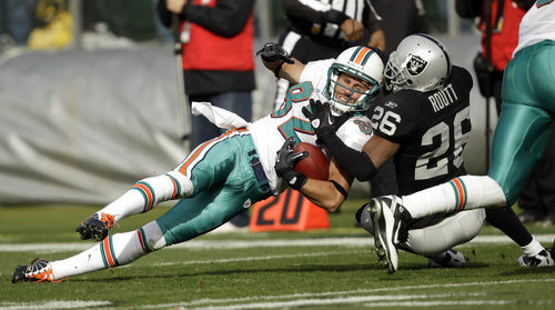 Oakland Raiders cornerback Stanford Routt (26) tackles Miami Dolphins wide receiver Brian Hartline (82) in the second quarter of an NFL football game in Oakland, Calif., Sunday, Nov. 28, 2010. (AP Photo/Marcio Jose Sanchez)