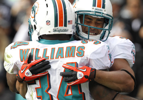 Miami Dolphins running back Patrick Cobbs, right, is congratulated by running back Ricky Williams (34) after scoring on a touchdown-pass against the Oakland Raiders in the first quarter of an NFL football game in Oakland, Calif., Sunday, Nov. 28, 2010. (AP Photo/Tony Avelar)