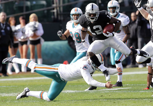Oakland Raiders wide receiver Jacoby Ford (12) jumps over Miami Dolphins placekicker Dan Carpenter (5) while returning the opening kickoff 101 yards for a touchdown in the first quarter of an NFL football game in Oakland, Calif., Sunday, Nov. 28, 2010. (AP Photo/Tony Avelar)