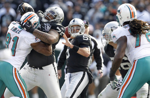 Oakland Raiders quarterback Bruce Gradkowski (5) passes against the Miami Dolphins in the second quarter of an NFL football game in Oakland, Calif., Sunday, Nov. 28, 2010. (AP Photo/Tony Avelar)
