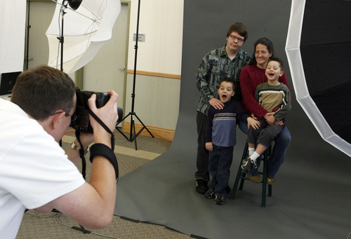 Francisco Kjolseth  |  The Salt Lake Tribune Photographer Ben Haslam takes a portrait shot of Jodi Davis and her three children, Zach, 16, Damien, 5, and Daunte, 4, at the Grace Mary Manor, a property of the Salt Lake County Housing Authority. Several volunteer photographers donated time to take professional portraits of those without means to pay, including homeless, low-income, single parents, seniors, military to give them a holiday portrait. Each party gets a 15-minute photo session and a edited CD with images. Everyone also gets a free 8X10.