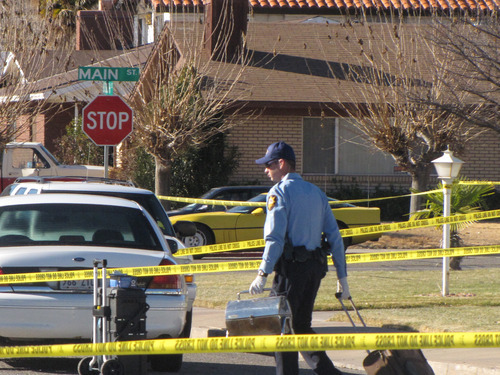Mark Havnes  |  The Salt Lake Tribune St. George police officer removes items from house where two women were killed by gunshots and a man was wounded early Saturday morning.
